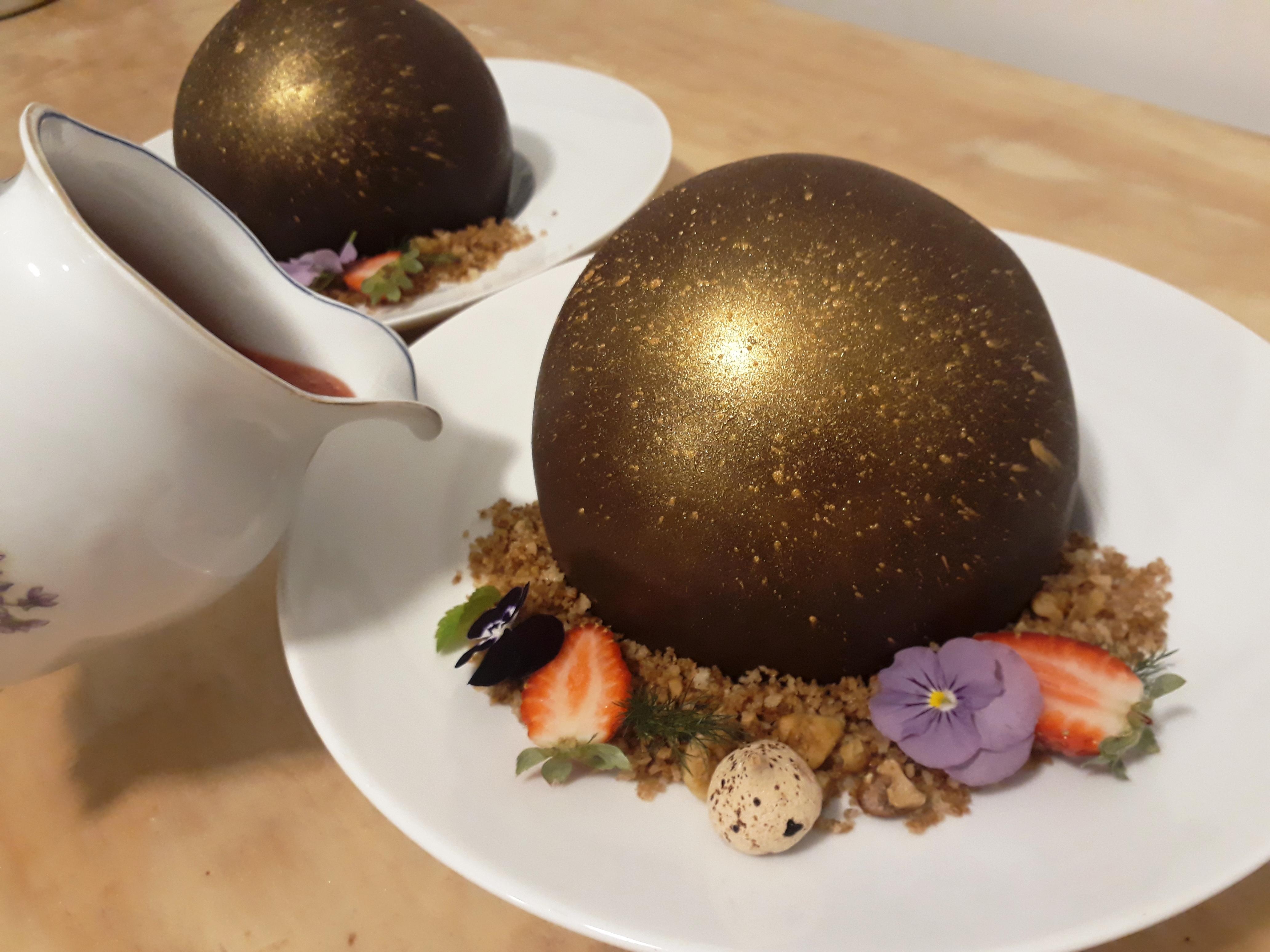 Esfera de chocolate surpresa com crumble de mel e especiarias e coulis de frutas vermelhas